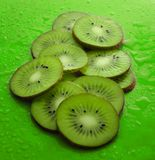 Slices of kiwi in water drops on a blue background. Fruit concept.  Royalty Free Stock Photo