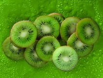 Slices of kiwi in water drops on a green background. Fruit concept.  Royalty Free Stock Photography