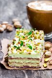 Slices  of layered cake  with pistachio and a cup of coffee with. Slices  of layered cake with pistachio and a cup of coffee with marshmallow Stock Photos