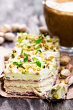 Slices  of layered cake with pistachio and a cup of coffee with. Marshmallow Royalty Free Stock Photo