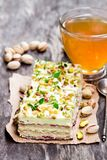 Slices  of layered cake with pistachio and a cup of green herbal. Tea Royalty Free Stock Photos