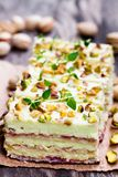 Slices  of layered  cake with pistachio on wooden background. Slices  of layered cake with pistachio on wooden background Royalty Free Stock Image