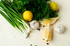 Slices of lemon, garlic cloves and parsley on the white backgrou Stock Images