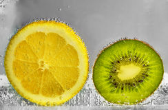 Slices of lemon and kiwi in water Stock Images