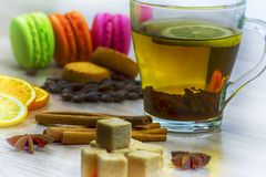 Slices of lemon and orange. Cup of tea with lemon. Coffee beans, ookies macaroon and pieces of sugar on the table stock image