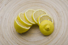 Slices of lemon on plate. Slices of lemon arranged on a wooden plate, cooking, preparing, cutting Stock Photo