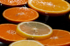 Slices of lemon and tangerine lying on water Stock Image