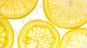 Slices of lemon in water with air bubbles. Background Stock Photography