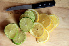 Slices of lemons and limes on blonde-tone cutting board Royalty Free Stock Image