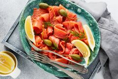 Slices of lightly salted salmon with capers, lemon and dill on a ceramic plate on a gray concrete background. Top view