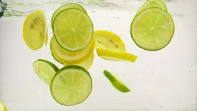 Slices of lime and lemon fall into a water with splashes and bubbles, slow motion close-up