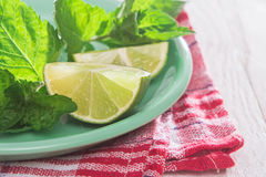 Slices of lime and mint on a plate. On a wooden table Royalty Free Stock Photography