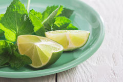 Slices of lime and mint on a plate. Slices of lime and mint on a wooden table Royalty Free Stock Photos