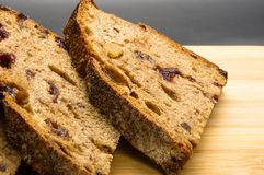 Slices of malt bread handmade. With nuts, raisins and cranberries on wooden background Royalty Free Stock Photography