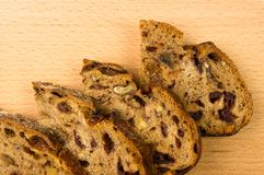Slices of malt bread handmade. With nuts, raisins and cranberries on wooden background Royalty Free Stock Photo