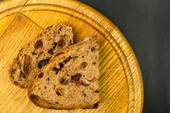 Slices of malt bread handmade. With nuts, raisins and cranberries on wooden background Stock Images