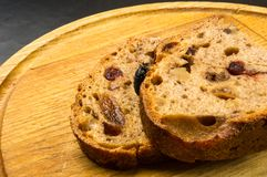 Slices of malt bread handmade. With nuts, raisins and cranberries on wooden background Stock Photos