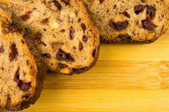 Slices of malt bread handmade. With nuts, raisins and cranberries on wooden background Royalty Free Stock Images