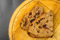 Slices of malt bread handmade. With nuts, raisins and cranberries on wooden background Stock Photo