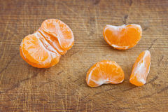 Slices of mandarin fruit. On the wooden background Stock Photos