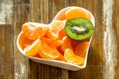 tangerine and kiwi in a white plate royalty free stock photo