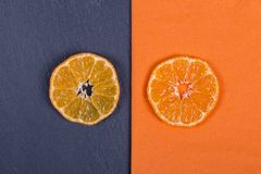 Slices of mandarin lies on orange napkin and on black slate. Concept of healthy, organic, vegan food, vitamins. Top view. Fresh or Stock Images