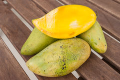 Slices mango in a pile of mango. In wood table Stock Images