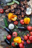 Slices of meat on the grill, on a wooden table with vegetables. Summer picnic in nature with delicious food. Royalty Free Stock Photos