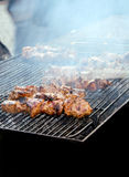Meat on stick grilling with smoke Royalty Free Stock Image