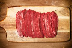 Slices of meat on a wooden board. And on a wooden table Royalty Free Stock Photography