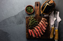 Slices medium rare beef steak with herb sauce, bottle of wine, copy cpace Stock Photo