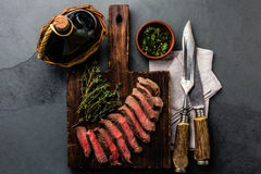 Slices medium rare beef steak with herb sauce, bottle of wine, vintage cutlery Royalty Free Stock Photography