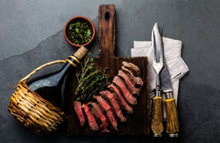 Slices medium rare beef steak with herb sauce, bottle of wine, vintage cutlery Stock Photos