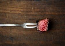 Slices of medium rare ribeye steak on meat fork on a dark wooden background. Slices of medium rare ribeye steak on meat fork Royalty Free Stock Image