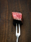 Slices of medium rare ribeye steak on meat fork on a dark wooden background Stock Photos