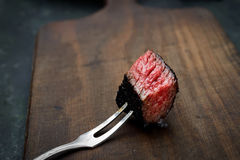 Slices of medium rare ribeye steak on meat fork on a dark wooden background Royalty Free Stock Photo