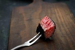 Slices of medium rare ribeye steak on meat fork on a dark wooden background. Slices of medium rare ribeye steak on meat fork Royalty Free Stock Photo