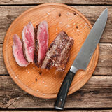 Slices of medium-rare steak. American cuisine. Slices of superior grilled meat served on round platter with big knife, on rustic wooden table, close up view Stock Photos