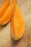 Slices of melon cantalupo. Fresh slices of melon cantalupo on a wooden cutting board Stock Photography