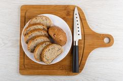 Slices of bread in white plate, knife on cutting board on table. Top view. Slices of multigrain bread in white plate, kitchen knife on bamboo cutting board on stock image
