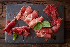 Slices Of Italian Prosciutto Crudo Or Jamon With Fresh Basil Leaves On A Black Background. Royalty Free Stock Photo