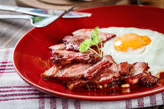 Slices Of Smoked Bacon And Fried Egg On A Red Plate Stock Photo