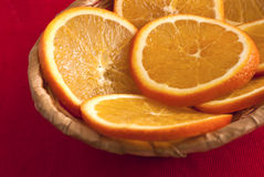 Slices of an orange in a basket. On red background Stock Image