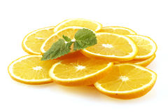 The slices of an orange decorated with lemon mint. Royalty Free Stock Photo