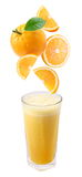 Slices of orange fall into a glass of fresh juice. stock photos