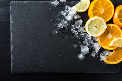 Slices of orange and lemon. With ice on stone black background. Summer food concept. Top view royalty free stock images