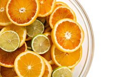 Slices of orange, lemon and lime in glass bowl Stock Images