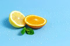 Slices of orange and lemon with mint leaves on a blue background with water drops. Summer cool water orange slices. Slices of orange and lemon on a blue royalty free stock photo
