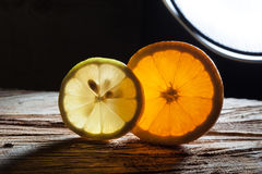 Slices of orange and lemon on rough wooden surface Royalty Free Stock Photos