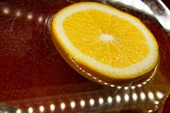 Slices of orange lie in the water next to the LEDs on. Light, orange and reflections royalty free stock photography